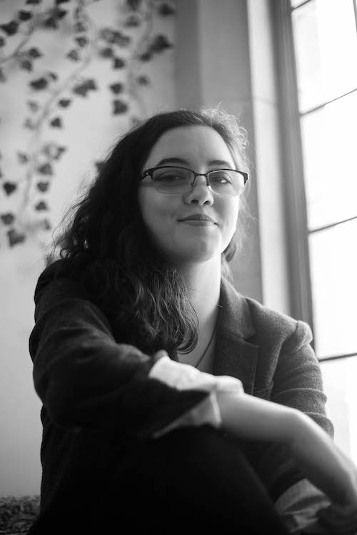 Image description: A black-and-white photo of Alex Brown sitting next to a window. She is a white woman with shoulder-length dark-brown hair and glasses. She is smiling slightly and wearing a blazer.